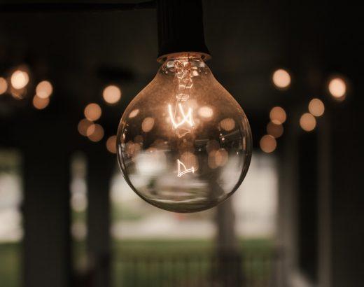 Im Zentrum des Bildes befindet sich eine Glühbirne. Im Hintergrund sind verschwommene Lichter zu sehen.