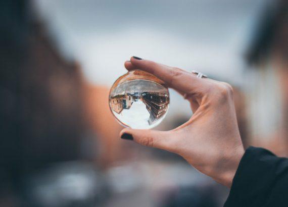 Eine Hand mit schwarz bemalten Fingernägeln hält eine durchsichtige Glaskugel fest, in dem Hintergrund auf dem Kopf steht. Der Hintergrund des Bildes zeigt eine Sackkasse mit Gebäuden.