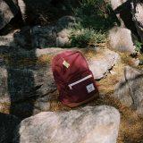 Das Bild zeigt einen roten Rucksack, der auf einem Felsen liegt.