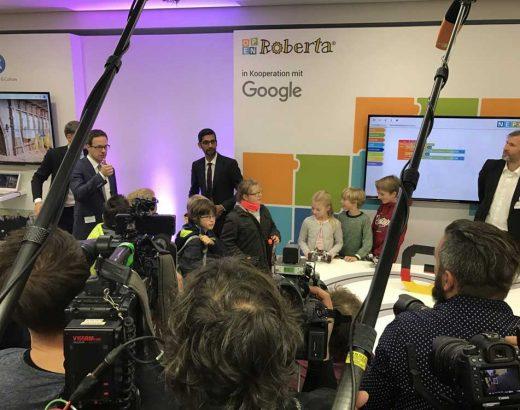 Das Bild zeigt den Moment der Präsentation des Projekts »Open Roberta«. Im Vordergrund sind Cameramänner und Fotografen zu sehen. Neben den Personen die das Projekt vorstellen, sind auch Kinder im Alter von 10 bis 12 Jahren anwesend.