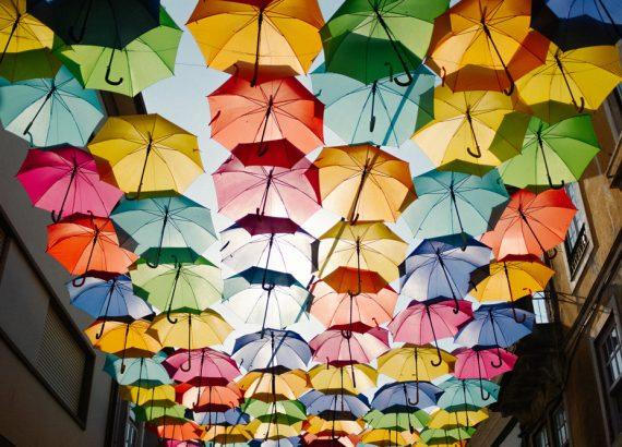 Entlang einer gesamten Straße sind hoch an den Gebäuden bunte Regenschirme in Sechserreihen an Schnürren befestigt.