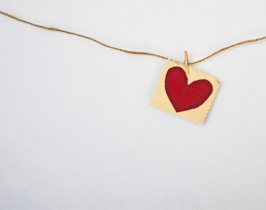 Marketing mit Herz – Eine braune Schnur hängt an einer weißen Wand. Mit einer kleinen Klammer wurde ein Zettel mit einem gemalten rotem Herz an die Schnur festgesteckt.