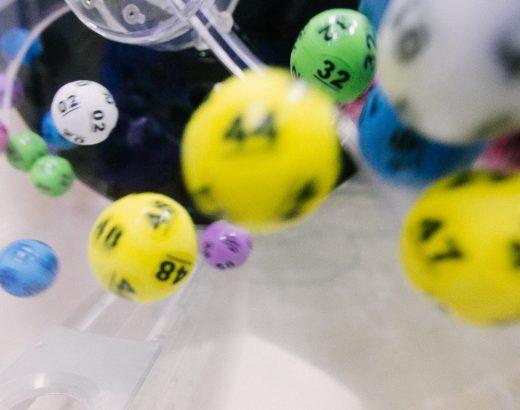 Das Bild zeigt bunte Lottokugeln, die in einem durchsichtigen Behälter gemischt werden.
