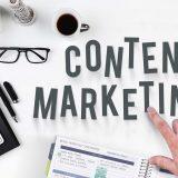 """Das Bild zeigt verschiedene Büroartikel, die auf einem Schreibtisch liegen. Eine Hand zeigt auf das Wort """"Content Marketing"""", das in Großbuchstaben geschrieben im Fokus des Bildes steht."""