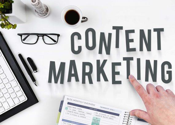 """Das Bild gehört zum Beitrag »Content-Strategie« und zeigt verschiedene Büroartikel, die auf einem Schreibtisch liegen. Eine Hand zeigt auf das Wort """"Content Marketing"""", das in Großbuchstaben geschrieben im Fokus des Bildes steht."""