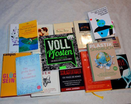 10 Bücher sind auf einem Tisch in zwei Reihen hingelegt. Fünf Bücher liegen verteilt auf der Reihe. Die Bücherthemen erstrecken sich von Romanen und Sachbüchern, die einen Mehrwert für die Menschen geben soll.
