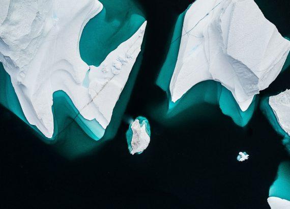 Drei Eisberge sind Frontal von oben fotografiert. Das Wasser wirkt fast schwarz und färbt sich nur an den Stellen Türkis, wo der Eisberg im Wasser liegt.