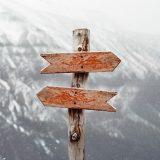 Das Bild zeigt einen Richtungspfeil aus Holz, der in den Bergen steht. Die Pfeile zeigen nach links und rechts.