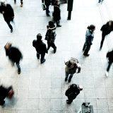 Marktforschung: Das Bild zeigt einige Menschen auf einem Platz. Teilweise sind die Personen verschwommen, da sie in Bewegung sind.