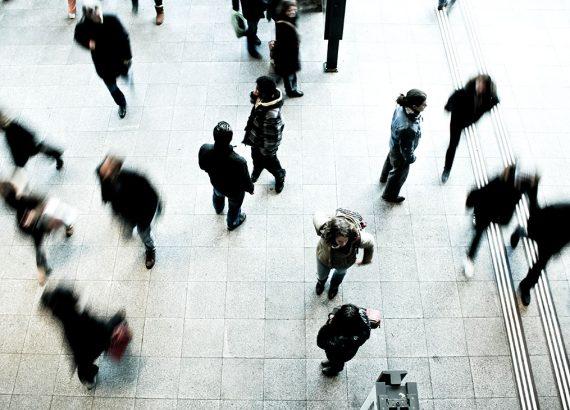 Das Bild zeigt einige Menschen auf einem Platz. Teilweise sind die Personen verschwommen, da sie in Bewegung sind.