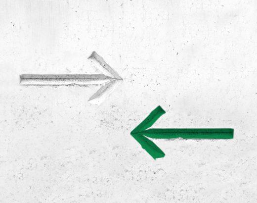 Auf weißem, strukturiertem Beton ist ein eingeritzter Pfeil von links nach recht zu sehen. Etwas rechts unten ist ein eingeritzter grüner Pfeil zu sehen. Die grüne Farbe soll die Menschen umleiten, wie das Thema Nudging.