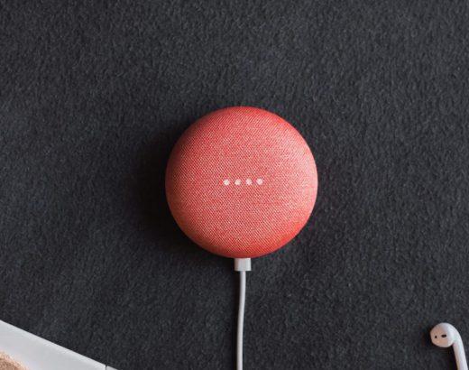 Auf dem Foto ist ein runder roter Sprachassistent, auf dem vier weiße Punkte zu sehen sind und zeigt hier die Verwendung von Voice Marketing. Die runde Box ist an einem weißen Stromkabel angesteckt und liegt auf einem dunkelblauen weichen Teppich. Am unteren Rand ist ein Schweißer Airpod zusehen.