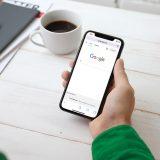 Ein Mann hält ein iPhone in der Hand. Auf dem Display ist die Suchmaschine Google zu sehen. Auf dem Tisch sind Blätter, Notizblöcke und eine Tasse Kaffee.