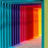 Ein Weg gemauert mit vielen farbigen Holzbretter. Durch das Licht werden die Farben auf den Boden reflektiert und soll die Wichtigkeit der Wahrnehmung, die die Farben im Marketing haben, Wiederspiegeln.