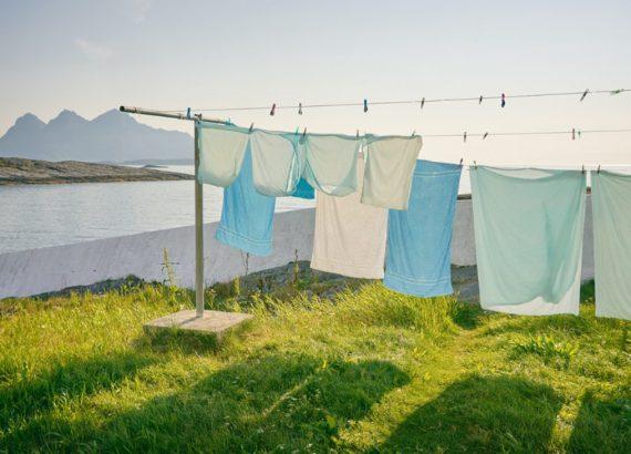 Greenwashing: Eine Wäscheleine mit pastellfarbener Wäsche bedeckt das Bild zu 3/4. Im Hintergrund sind Berge zu sehen.