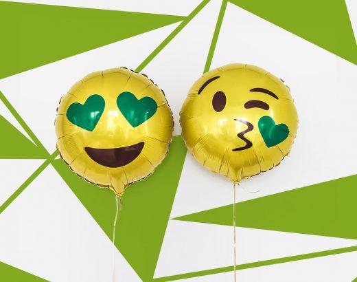 Es sind zwei Luftballon mit Emoji-Motiven. Der linke Luftballon ist rund, gelb und das Emoji hat einen offenes lachen. Die Augen sind zwei grüne Herzen. Der rechte Luftballon hat ein Kussmund geformt woraus ein grünes Herz kommt. Die Augen zwinkern einem zu. Diese Smiley werden im Emoji-Marketing eingesetzt.