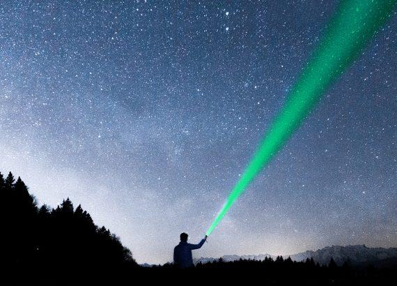 Ein Mann strahlt mit einer Taschenlampe in den Sternenhimmel auf der Suche nach einer »Marketingstrategie«