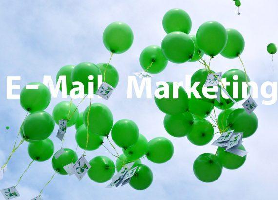 Grüne Luftballons mit einer grün-gelblichen Schnurr, an dem eine Postkarte befestigt steht. In großer Schrift steht mitten auf dem Bild geschrieben »E-Mail-Marketing«